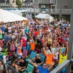 Crowd of people waving at the camera during white marlin open day