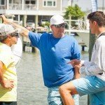 Three guys standing on a dock during the day talking in Ocean City MD