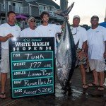 Group of guys standing around their 177 lb tuna fish during white marlin opening day