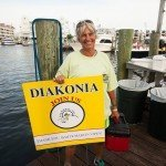 Lady holding a diakonia sign in one hand and a tackle box in the other in OC MD