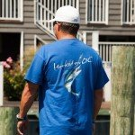 Man on a dock wearing a Hooked on OC blue shirt in OC MD