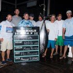 Eight guys standing around their upside down tuna during white marlin open 2015