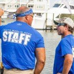 Two staff members in blue shirts talking during white marlin open 2015