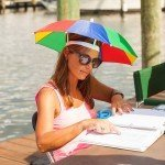 Woman in an umbrella hat looking through a notebook during White Marlin Open