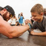 Guy and young boy arm wrestling during White Marlin Open 2015