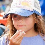 Close up of a young girl wearing a hat and holding some popcorn