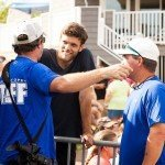 Two staff members of the white marlin open 2015 talking to a guy in a black shirt