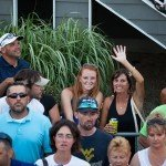 Woman holding a canned drink and waving at the camera during white marlin open