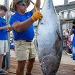 Staff member for white marlin open hanging up a big tuna