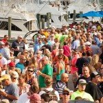 Crowd of people standing on a dock with fishing boats in the background in Ocean City MD