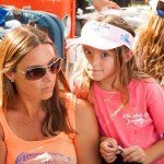 Young girl in a pink shirt standing with her mother during white marlin open 2015