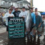 155 pound tuna hanging upside down surrounded by the men that caught it for white marlin open