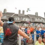Guy in grey shirt throwing gifts into the air over a crowd for white marlin open