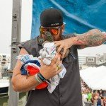 Man holding a bunch of different clothing giveaways for white marlin open 2015