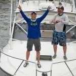 Two guys standing on the bow of a fishing boat with one of them posing in Ocean City MD