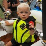 Young blonde boy in a fishing seat on a fishing boat during white marlin open 2015