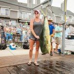 Woman standing with her mahi mahi fish on a dock in Ocean City MD