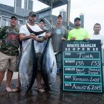 Crew of the Restless Lady fishing boat holding their two tuna fish on a dock in Ocean City MD