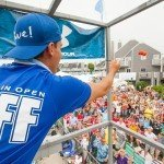 Staff member of the white marlin open standing above the crowd and holding out his arm