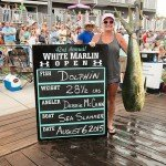 Angler Debbie McCann standing with a mahi mahi dolphin during white marlin open 2015