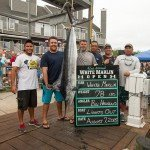 Lights out fishing boat's crew surrounding their white marlin on a dock in Ocean City MD