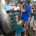 Young boy standing next to and putting his arm in the near the 200 pound tuna in OC MD