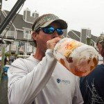 Guy in camo visor drinking fireball whiskey right from the bottle during white marlin open