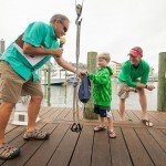 Speaker giving a young boy a bag on a dock during white marlin open 2015