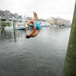 Man in blue trunks doing a backflip into the water in Ocean City MD